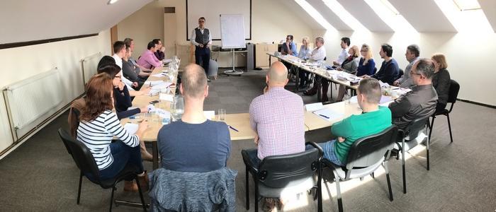 Peter Urbanec rozpráva pri flipcharte účastníkom tréningu, semináru